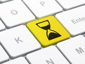 Time concept: Hourglass on computer keyboard background — Stock Photo