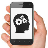 Marketing concept: Head With Gears on smartphone — Stock Photo