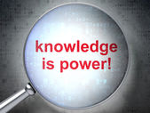 Education concept: Knowledge Is power! with optical glass — Stock Photo