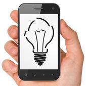 Finance concept: Light Bulb on smartphone — Stock Photo