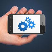 Web development concept: Gears on smartphone — ストック写真