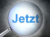 Time concept: Jetzt(german) with optical glass on digital backgr — Stock Photo