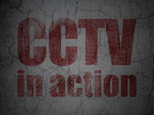 Protection concept: CCTV In action on grunge wall background — Stockfoto