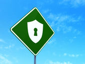 Privacy concept: Shield With Keyhole on road sign background — Stock Photo
