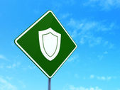 Security concept: Shield on road sign background — Stock Photo
