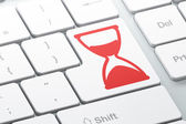 Time concept: Hourglass on computer keyboard background — Stok fotoğraf