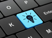 Business concept: Light Bulb on computer keyboard background — Stockfoto
