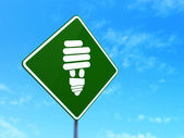 Business concept: Energy Saving Lamp on road sign background — Zdjęcie stockowe