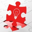 Foto Stock: Finance concept: Light Bulb on puzzle background