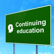 Education concept: Continuing Education and Head With Keyhole on road sign background — Stock Photo
