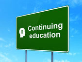 Education concept: Continuing Education and Head With Keyhole on road sign background — Foto de Stock