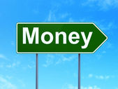 Finance concept: Money on road sign background — Stock Photo