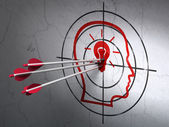Business concept: arrows in Head With Lightbulb target on wall background — Stock Photo