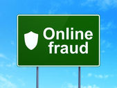 Safety concept: Online Fraud and Shield on road sign background — Zdjęcie stockowe