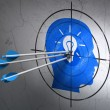 Data concept: arrows in Head With Light Bulb target on wall background — Stockfoto