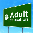 Education concept: Adult Education and Head With Finance Symbol on road sign background — Stock Photo