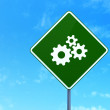 Marketing concept: Gears on road sign background — Stock Photo