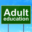 Education concept: Adult Education on road sign background — Stock Photo