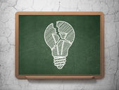 Finance concept: Light Bulb on chalkboard background — Stock Photo