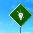 Business concept: Light Bulb on road sign background — Stock Photo