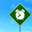 Time concept: Alarm Clock on road sign background — Stock Photo