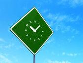 Conceito de linha do tempo: relógio no fundo do sinal de estrada — Fotografia Stock
