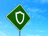 Safety concept: Contoured Shield on road sign background — Stock Photo