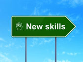 Education concept: New Skills and Head With Finance Symbol on road sign background — Stock Photo