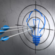 Business concept: arrows in Light Bulb target on wall background — Stock Photo