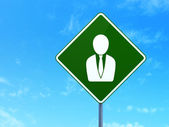Advertising concept: Business Man on road sign background — Stock Photo