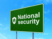 Security concept: National Security and Shield on road sign background — Stock Photo