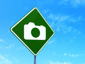 Vacation concept: Photo Camera on road sign background — Stok fotoğraf