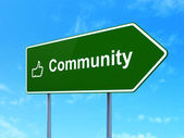 Social network concept: Community and Thumb Up on road sign background — Foto de Stock