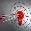 Finance concept: arrows in Light Bulb target on wall background — Stock Photo