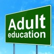 Stock Photo: Education concept: Adult Education on road sign background