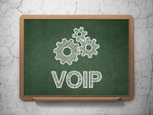 Web development concept: Gears and VOIP on chalkboard background — Stock Photo