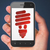 Finance concept: Energy Saving Lamp on smartphone — Foto de Stock