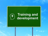 Education concept: Training and Development and Head With Lightbulb on road sign background — Foto de Stock