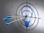 Unser geschäftskonzept: pfeile in der glühbirne-ziel auf wand-hintergrund — Stockfoto