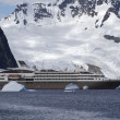 Tourist liner sailing among icebergs in Antarctica on a backgrou — Stock Photo #48996595