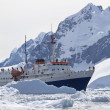 Tourist ship among the icebergs on the background of the mountai — Stock Photo #48996611
