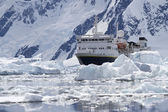 Big blue tourist ship in the ice in the background of the Antarc — Stock Photo