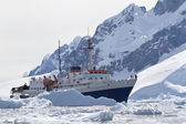 Tourist ship among the icebergs on the background of the mountai — Stock Photo