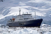 Big blue tourist ship in Antarctic waters against the backdrop o — Stockfoto