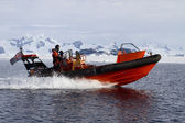 Orange boat sailing at high speed in Antarctic waters against mo — Stock Photo