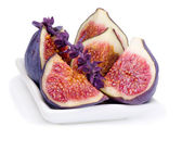 Some juicy, ripe slices of fig and basil flower — Stock Photo
