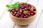 Cowberry with green leaflets in wooden cup — Stock Photo
