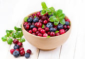Blueberry and cowberry with green leaflets in wooden cup — Stock Photo