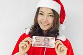 Christmas woman wearing santa hat and holding money — Stock Photo