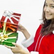 Santa claus girl giving gift box in hands over white — Stock Photo #14871611